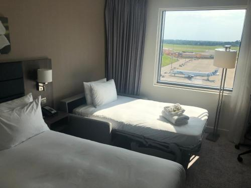 A bed or beds in a room at Hilton Garden Inn Birmingham Airport Uk