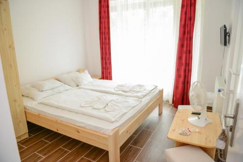 A bed or beds in a room at Thermal Panzió Igal