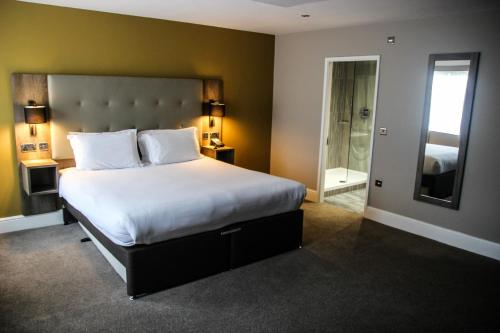 A bed or beds in a room at Crabwall Manor Hotel & Spa