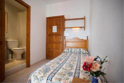 A bed or beds in a room at Hostal Sa Rota