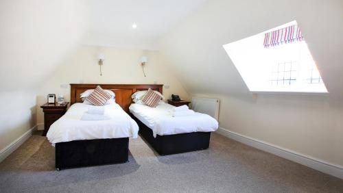 A bed or beds in a room at The Bishops Table Hotel