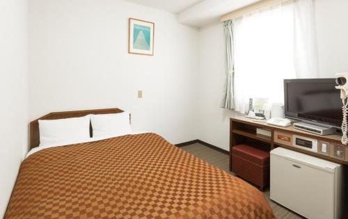 A bed or beds in a room at Matsue New Urban Hotel