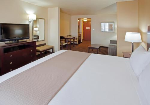 A bed or beds in a room at Holiday Inn Express Hotel & Suites Dinuba West