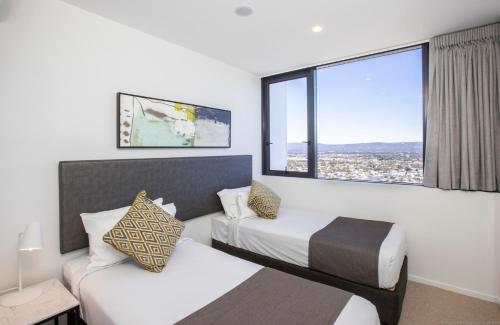 A bed or beds in a room at Qube Broadbeach
