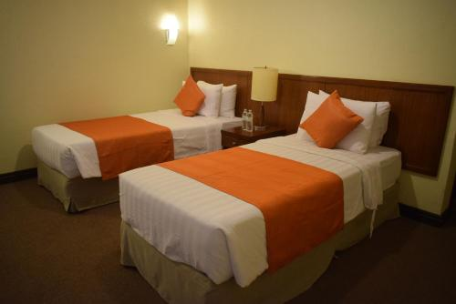 A bed or beds in a room at The Suites At Mount Malarayat