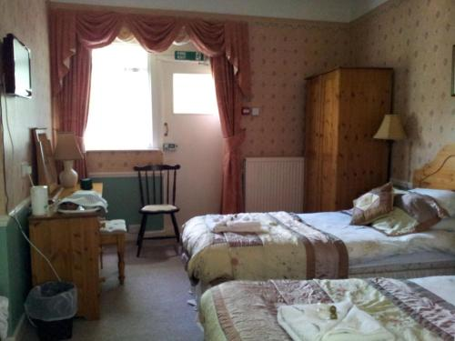 A bed or beds in a room at Roseglen Hotel