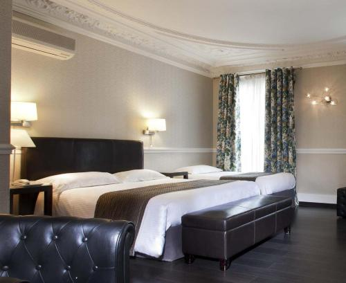 A bed or beds in a room at Hotel Claude Bernard Saint-Germain