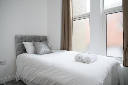 A bed or beds in a room at TLK Apartments & Hotel - Beckenham