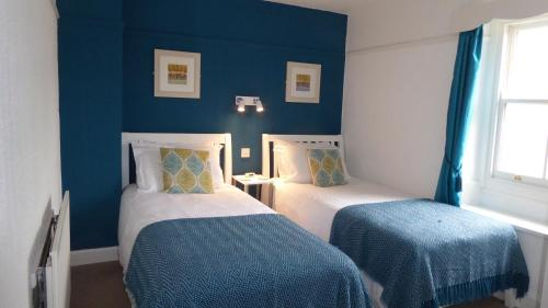 A bed or beds in a room at Rosegarth Guest House
