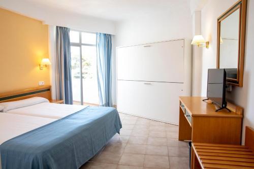 Łóżko lub łóżka w pokoju w obiekcie Gavimar Cala Gran Hotel and Apartments