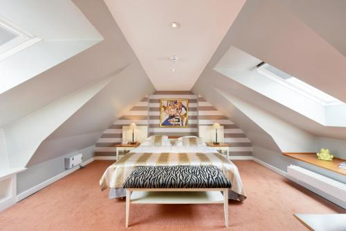 A bed or beds in a room at Relais & Châteaux Landhaus Stricker