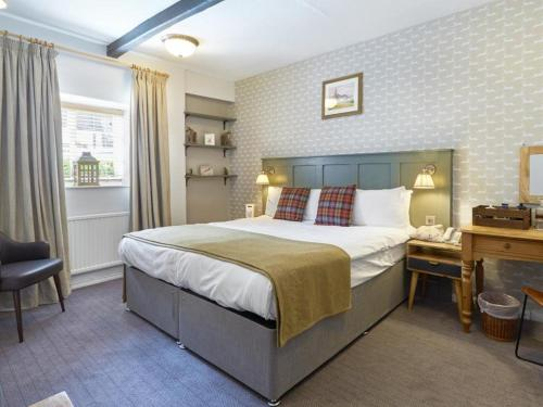 A bed or beds in a room at Redesdale Arms Hotel