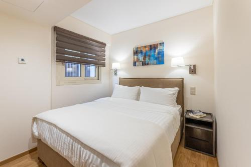A bed or beds in a room at Olygreen Athens Residences