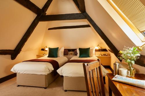 A bed or beds in a room at The Greyhound Inn