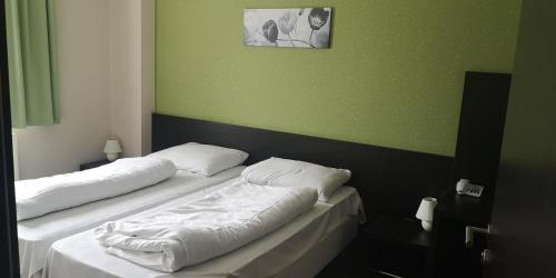 A bed or beds in a room at WHB Hotel