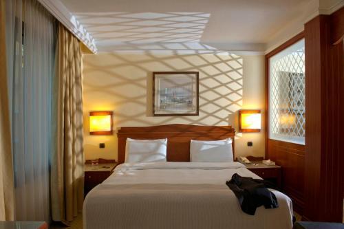 سرير أو أسرّة في غرفة في راديسون بلو مارتينيز بيروت