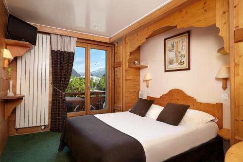 A bed or beds in a room at Hôtel de L'Arve