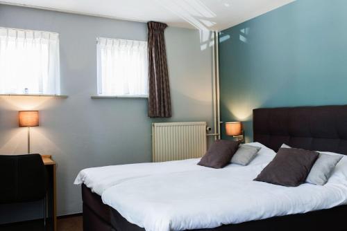 Een bed of bedden in een kamer bij Hotel 't Paviljoen