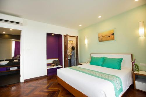 A bed or beds in a room at ÊMM Hotel Hue