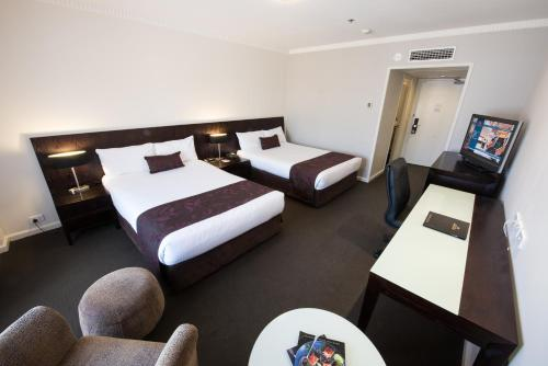 A bed or beds in a room at Hotel Grand Chancellor Adelaide