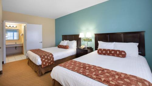 A bed or beds in a room at staySky Suites I-Drive Orlando Near Universal