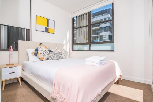 A bed or beds in a room at Serene Leichhardt 2bed2bath APT (Lewisham Station)