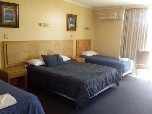 A bed or beds in a room at Desert Sand Motor Inn