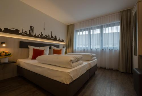 A bed or beds in a room at Garni Hotel Schumacher