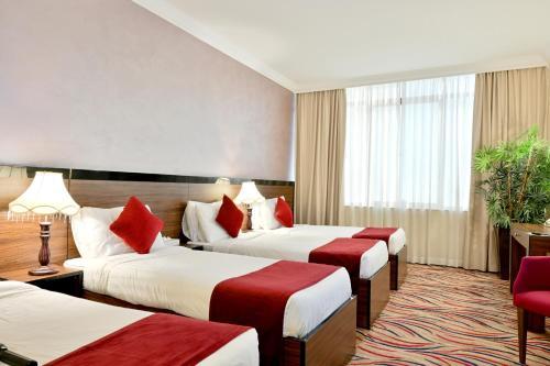 سرير أو أسرّة في غرفة في فندق حياة الذهبي