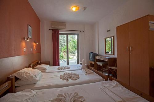 A bed or beds in a room at Apostolis Hotel Apartments