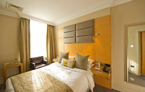 A bed or beds in a room at Woodlands Park Hotel