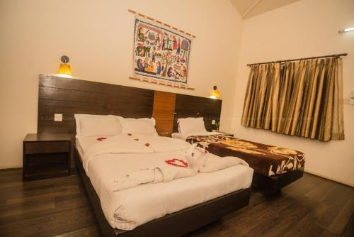 A bed or beds in a room at Chitwan Adventure Resort