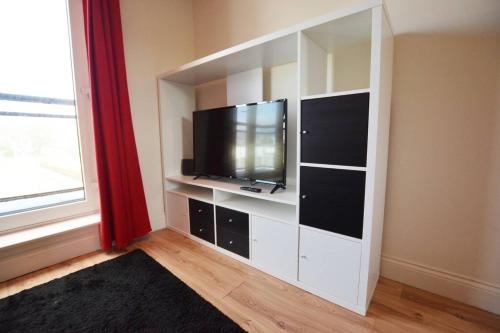 A television and/or entertainment center at The Heart of Southampton at 18East - Balcony View