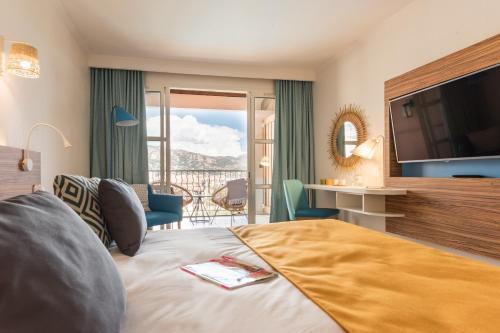 A bed or beds in a room at Hôtel de l'Esterel
