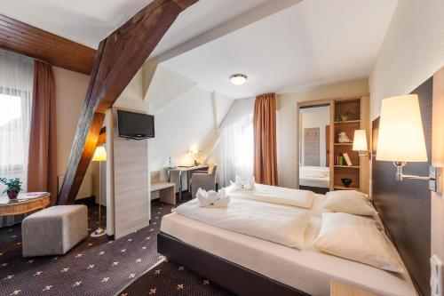 A bed or beds in a room at Hotel & Restaurant Hessischer Hof