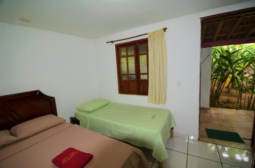 A bed or beds in a room at Doce Lar Hospedaria