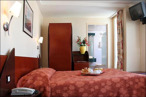 A bed or beds in a room at Pavillon Villiers Etoile