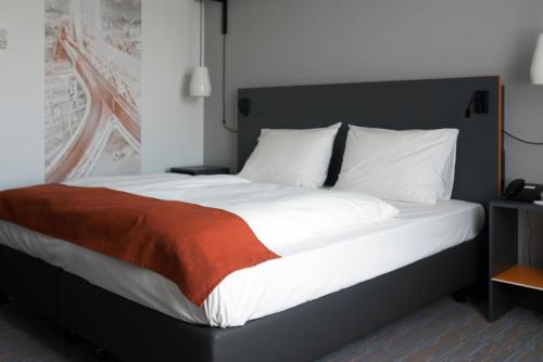 A bed or beds in a room at Vienna House Easy Airport Bucharest