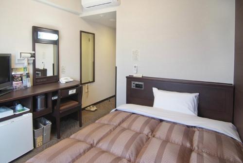 Un ou plusieurs lits dans un hébergement de l'établissement Hotel Route-Inn Toki
