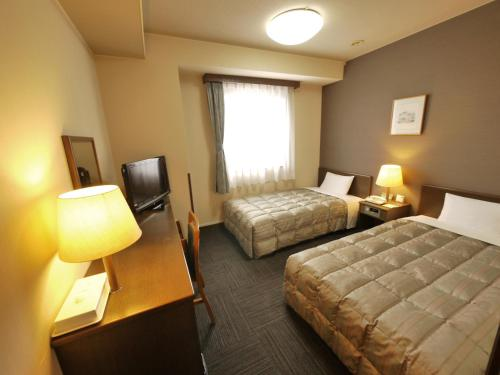 A bed or beds in a room at Hotel Route-Inn Minokamo