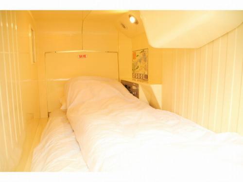Tempat tidur dalam kamar di Capsule Inn Fujisan