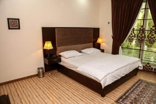 A bed or beds in a room at Monarch Residency
