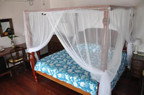 A bed or beds in a room at Petite Anse Hotel