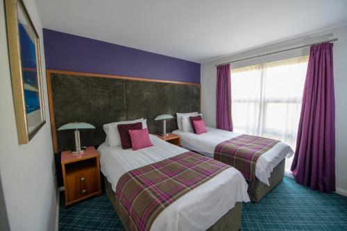 A bed or beds in a room at Loch Lomond Waterfront Luxury Lodges