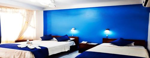 A bed or beds in a room at Paititi Hostal