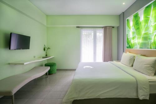 A bed or beds in a room at EDEN Hotel Kuta Bali