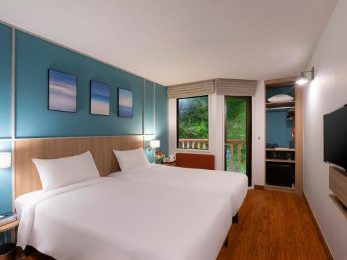 A bed or beds in a room at Ibis Phuket Patong