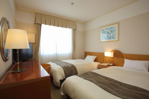 A bed or beds in a room at The Celecton Premier Kobe Sanda Hotel