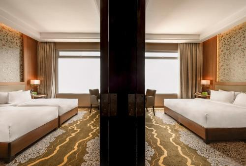 A bed or beds in a room at The Wembley – A St Giles Hotel, Penang
