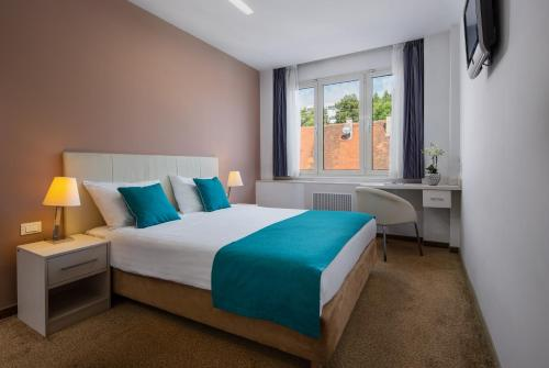 A bed or beds in a room at Hotel Jadran